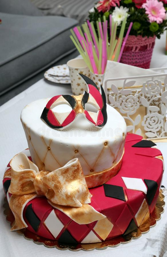 Birthday cake decorated with mask and bow. Birthday homemade cake decorated with mask and bow stock image