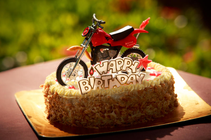 Birthday cake decorated with motorcycle and red stars. Birthday cake with nuts and vanilla cream decorated with motorcycle figure, red stars and words Happy stock photo