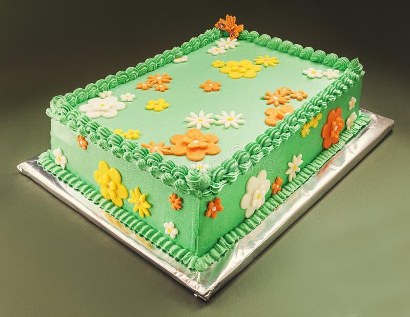 Birthday Cake. Decoration of a birthday cake, symbolizes green field with yellow, orange and white flowers stock photo