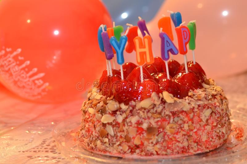 Birthday cake. Delicious cheesecake birthday cake with Happy Birthday candles and balloons royalty free stock photography