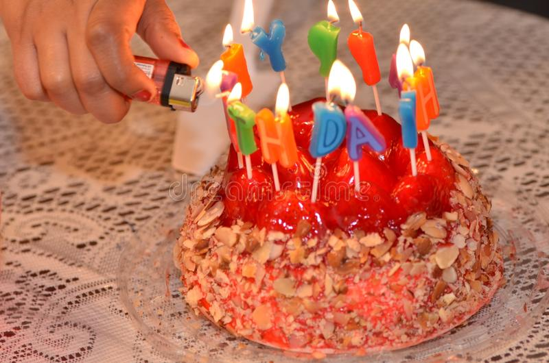 Birthday cake. Delicious cheesecake birthday cake with Happy Birthday candles and balloons stock images