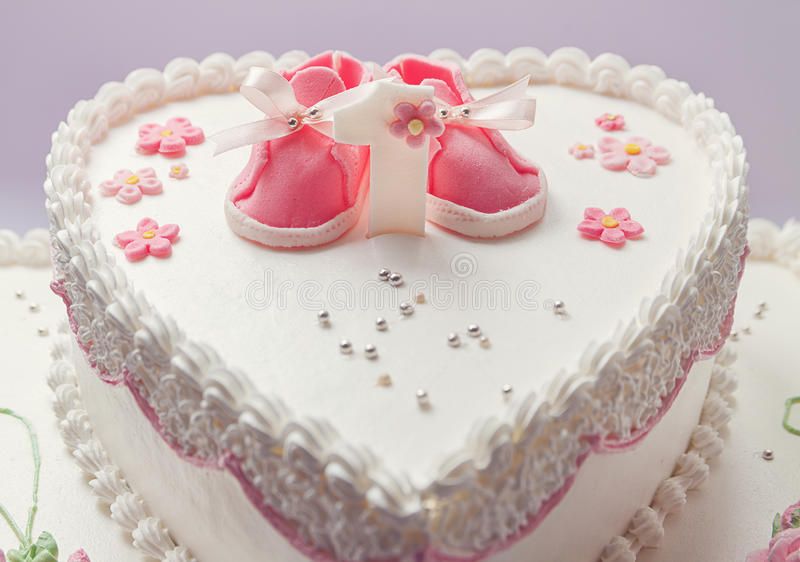 Birthday Cake. Details of a birthday cake for baby girl, number one and sweet sugar shoes on top stock images