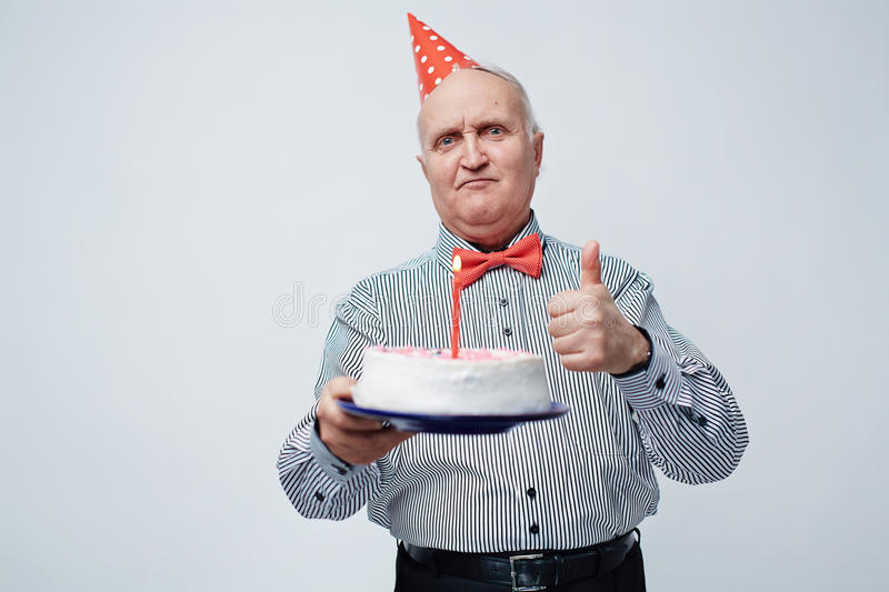 Birthday Cake for Elderly Man. Waist up portrait of satisfied and festively dressed old man in birthday cap showing thumbs-up and holding cake with candle royalty free stock photo