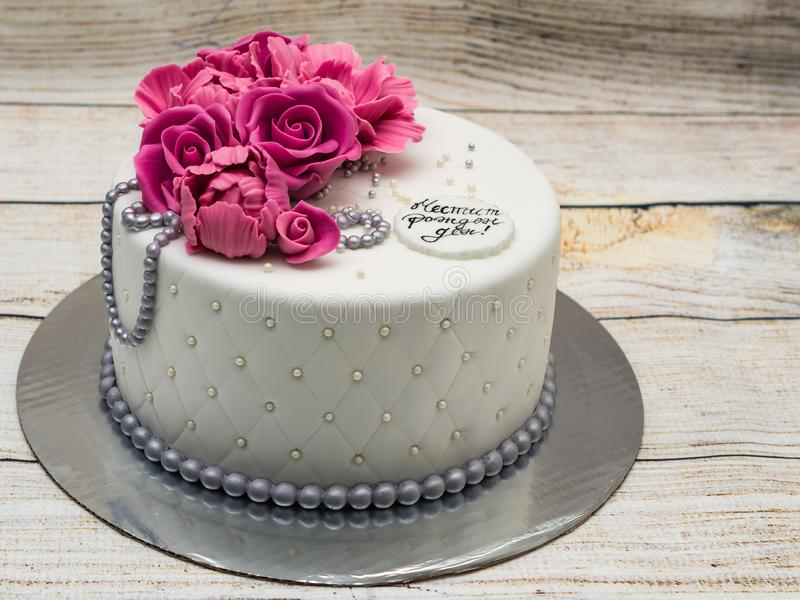 Birthday cake with fondant flowers - roses and peonies and silver pearls. Inscription `Happy Birthday`. Birthday cake with flowers - roses and peonies and silver stock photography