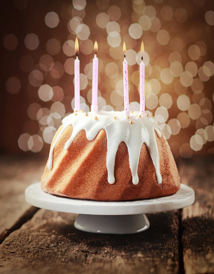 Birthday cake with four burning candles. Birthday cake glazed with dripping icing sugar and decorated with pearls topped with four burning candles against a royalty free stock photography