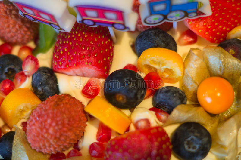 Birthday cake with fresh fruit and berries. Decorated with childish candles on birthday royalty free stock images