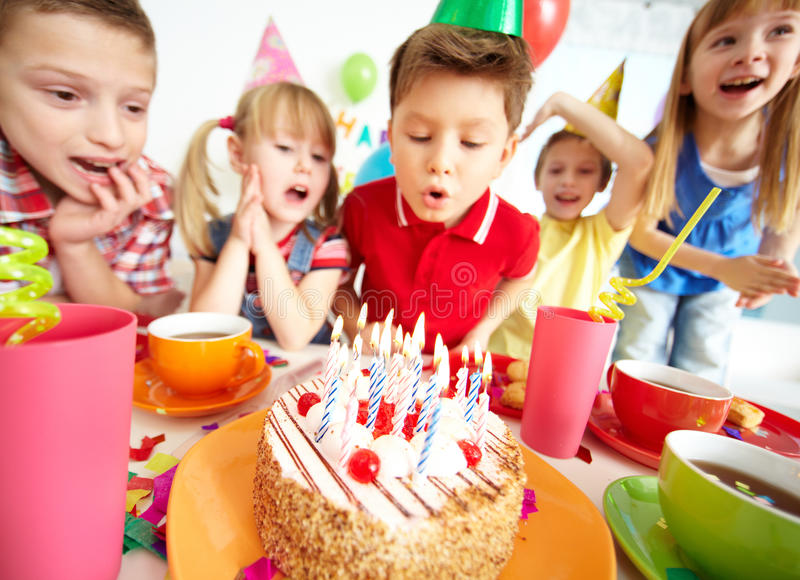 Birthday cake. Group of adorable kids looking at birthday cake with candles stock photos
