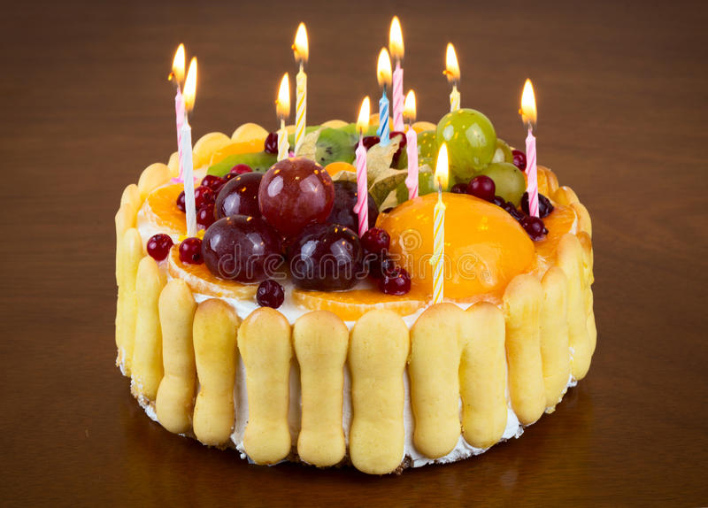 Birthday cake. Happy birthday fruit cake with candles on wooden table background stock image