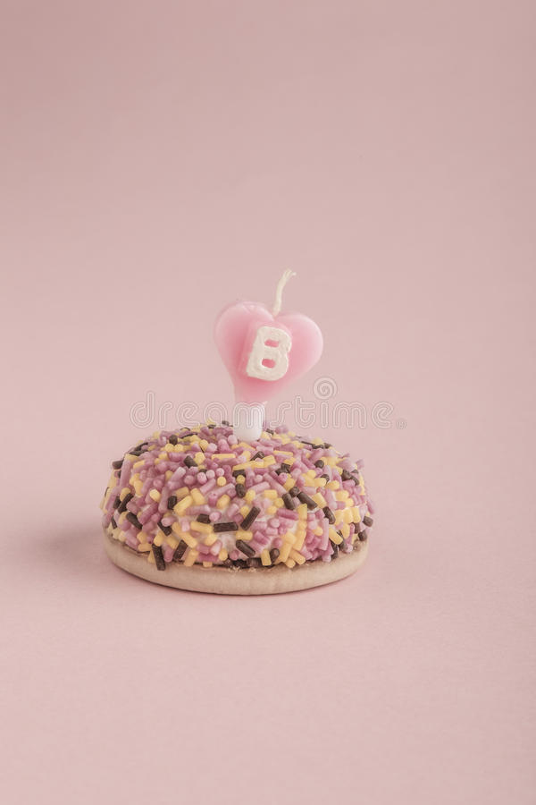 Birthday cake with heart shaped candle on pink royalty free stock images