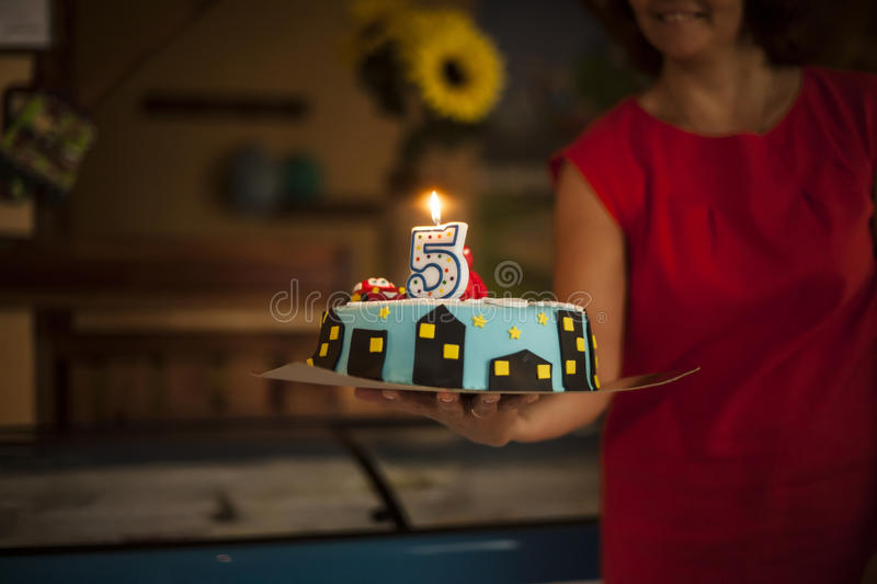 Birthday Cake with Lighting Candle. On female hand stock photo