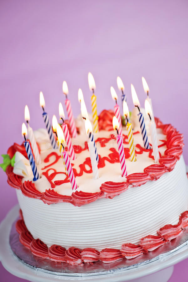 Birthday cake with lit candles. Birthday cake with burning candles on a plate on pink background stock images
