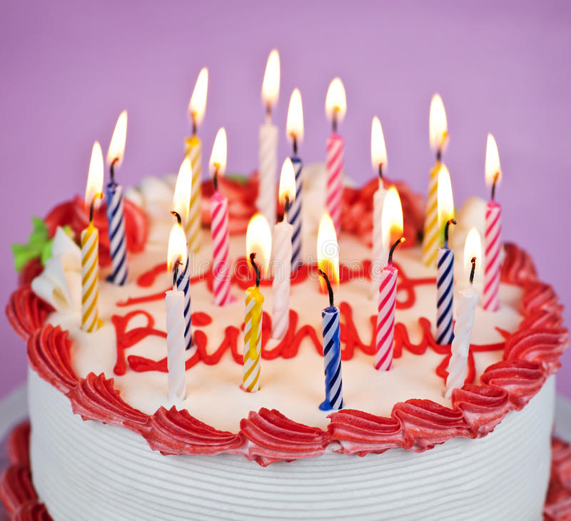 Birthday cake with lit candles. Birthday cake with burning candles and icing stock photos