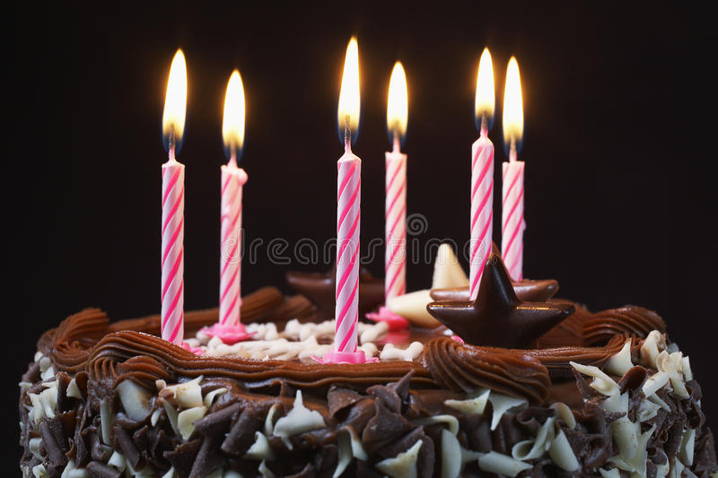 Birthday Cake With Lit Candles. Closeup of a birthday cake with lit candles royalty free stock image