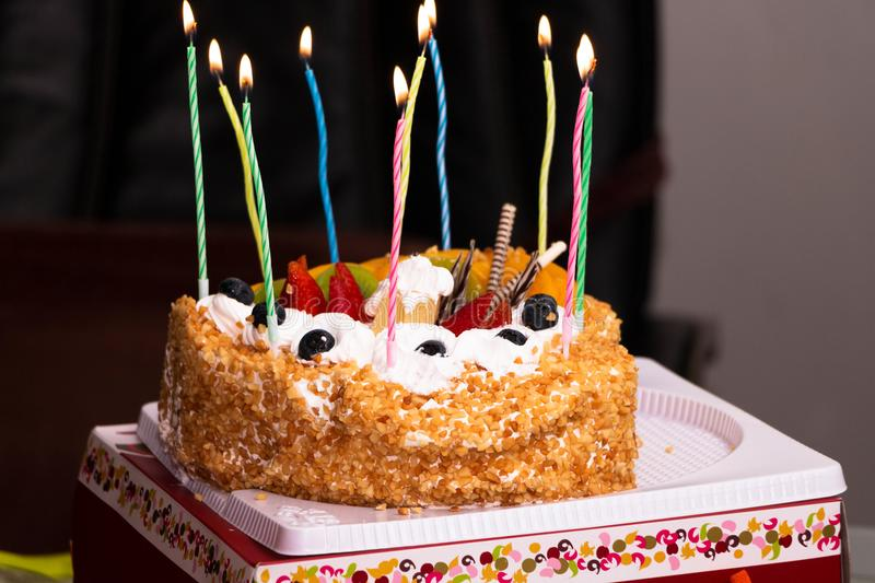 A birthday cake lit with candles royalty free stock image