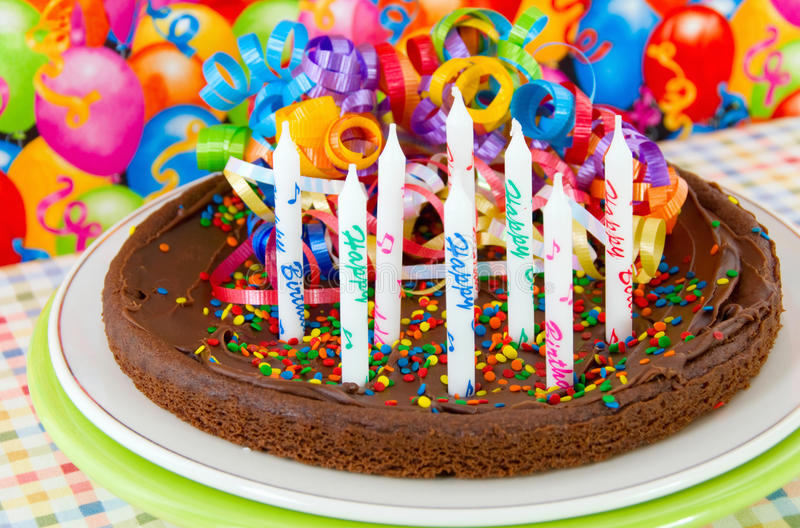 Birthday cake. Made with brownies and sprinkles. Unlit candles on top with a festive balloon background royalty free stock photos
