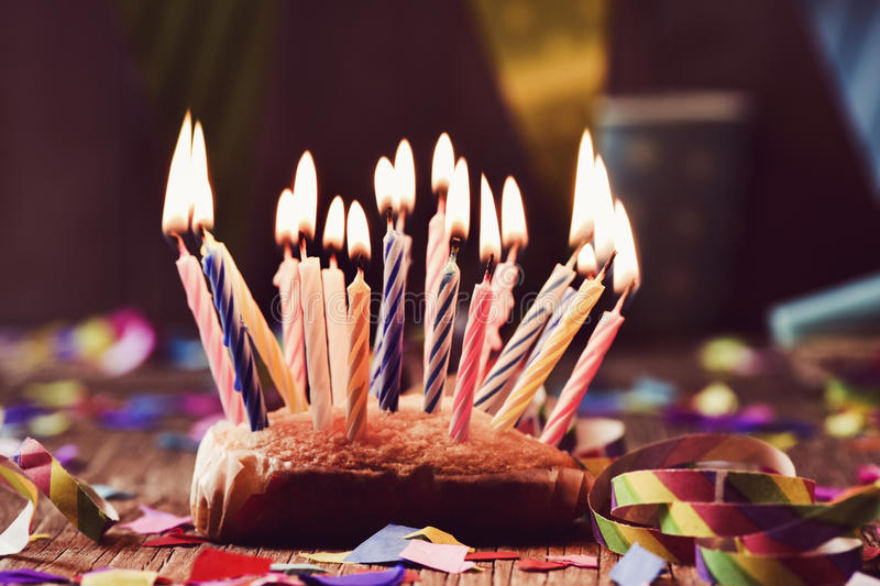 Birthday cake with many lit candles. A small cake topped with some lit candles before blowing out the cake, on a rustic wooden table, sprinkled with confetti and royalty free stock photo