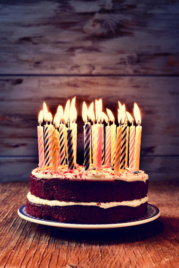 Birthday cake with many lit candles. A cake topped with some lit candles before blowing out the cake, on a rustic wooden table, against a blue wooden background stock photography