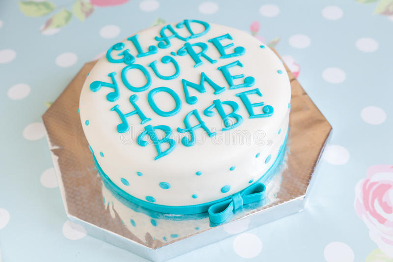 Birthday Cake with mastic text. Birthday Cake with blue dots and mastic text Glad You're Home Babe on floral background stock photo