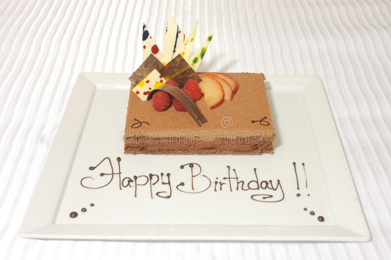 Birthday cake mousse. On a white plate decorated with white chocloate and fruit stock photos