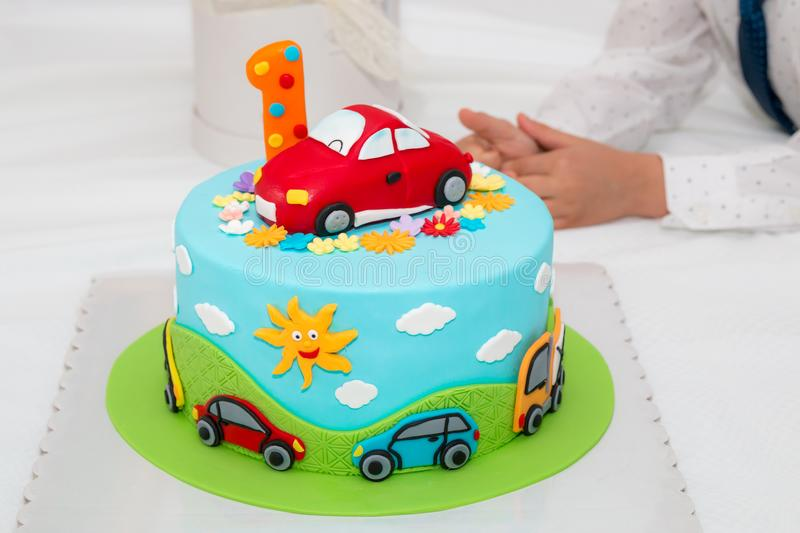 Birthday cake with number one. Children`s colorful fondant birthday cake decorated with little cars and number one on the top royalty free stock photos