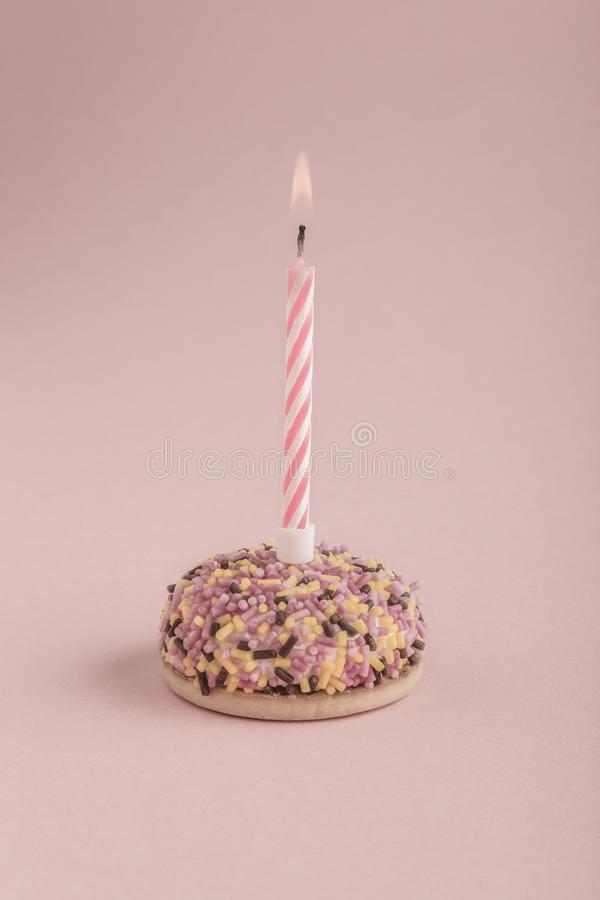 Birthday cake with one candle on pink royalty free stock photos