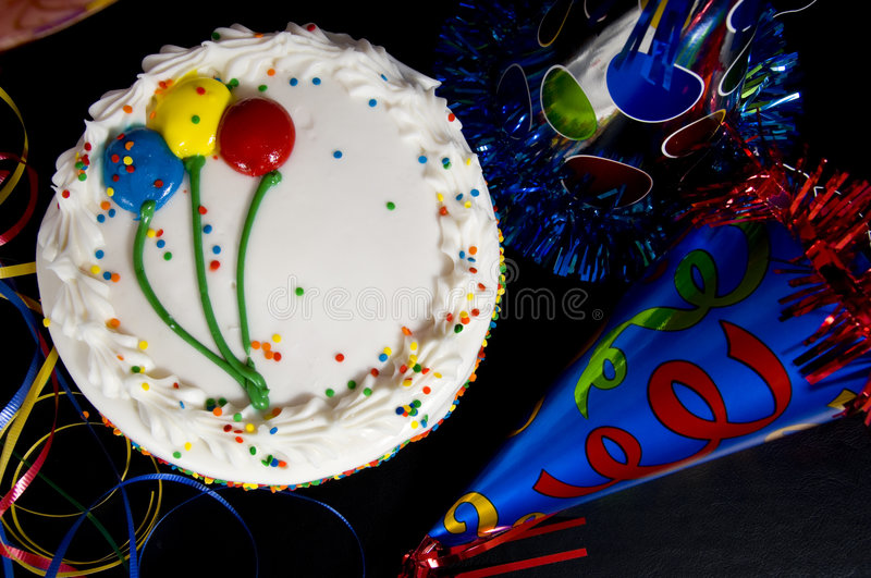 Birthday Cake and Party Hats. A white birthday cake surrounded by colorful party hats and ribbon streamers stock photos
