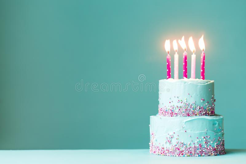Birthday cake with pink candles. Tiered birthday cake with pink candles and sprinkles stock photography