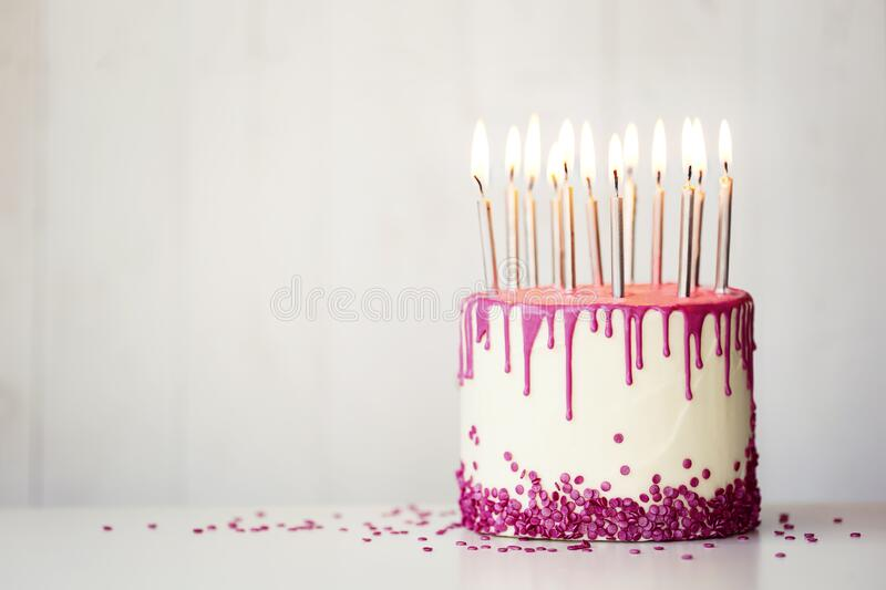 Birthday cake with pink drip icing and candles royalty free stock image
