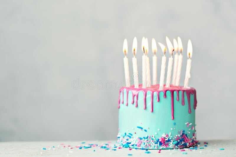 Birthday cake with pink drip icing and ten candles stock photo