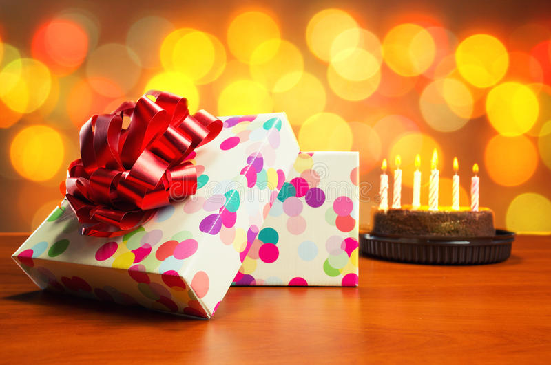Birthday cake and presents. Birthday cake with candles and present-box on the table stock photos