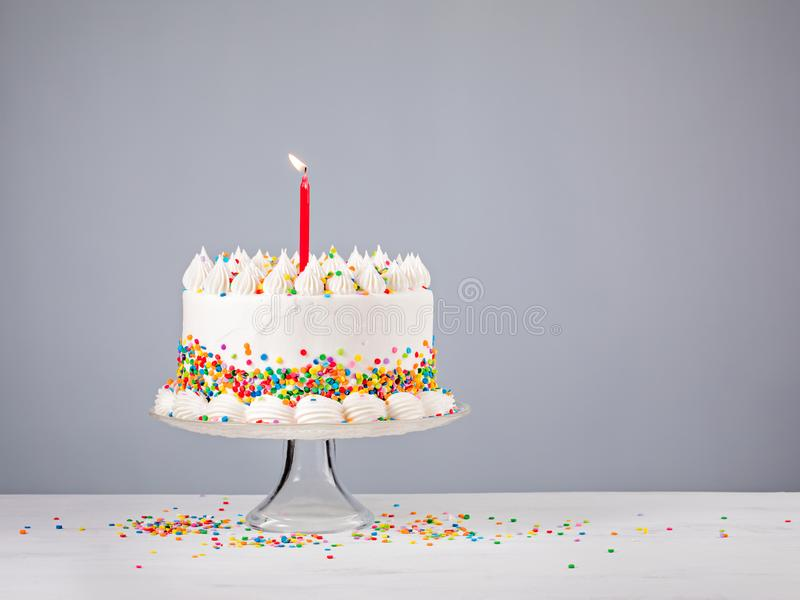 Birthday Cake with Red Candle. White Birthday cake with colorful Sprinkles and red candle over a gray background royalty free stock photo