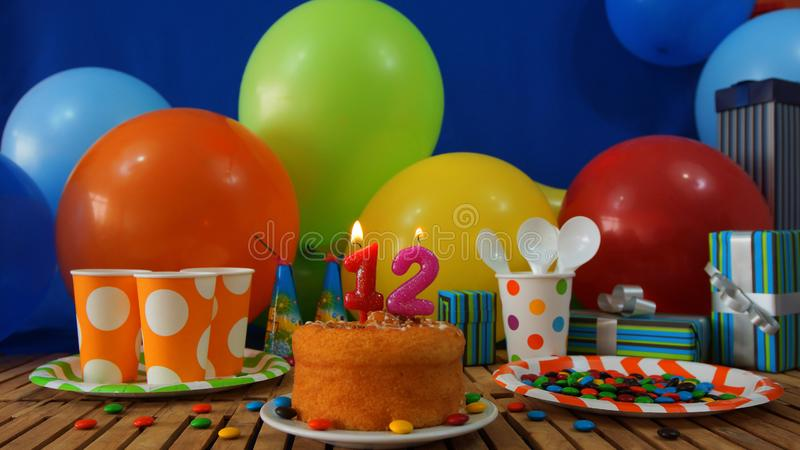 Birthday 12 cake on rustic wooden table with background of colorful balloons, gifts, plastic cups, plastic plate. Birthday 12 cake on rustic wooden table with stock photo