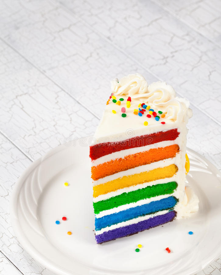 Birthday Cake. Slice of colourful rainbow layered birthday cake decorated with sprinkles and buttercream icing.Copy Space for your text royalty free stock photography