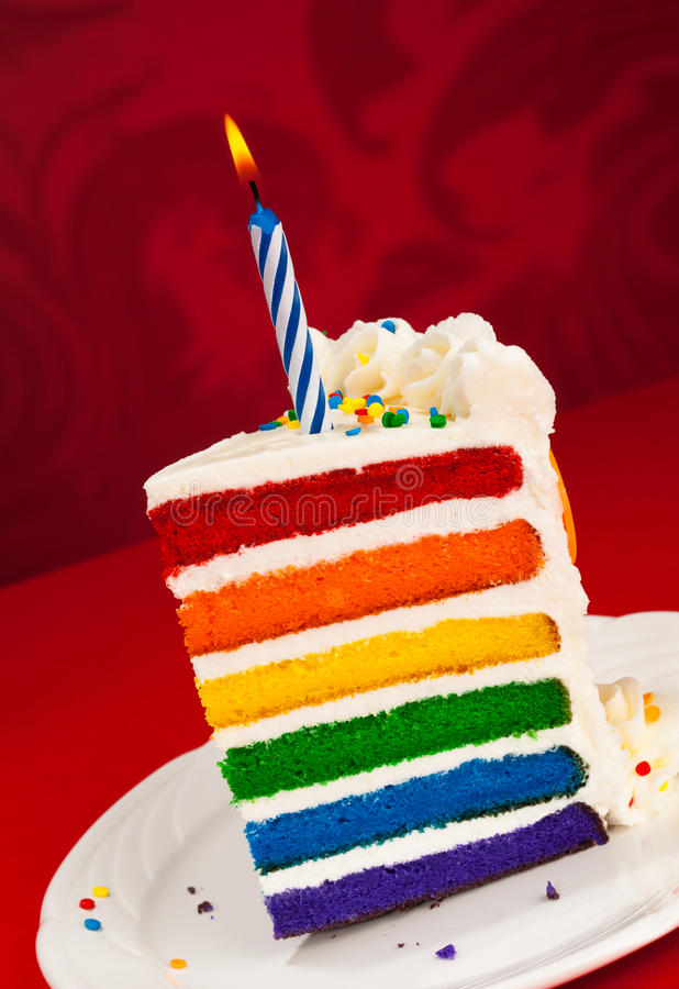 Birthday Cake. Slice of fun rainbow layered birthday cake decorated with sprinkles and buttercream icing with lit birthday Candle over a red background royalty free stock photos