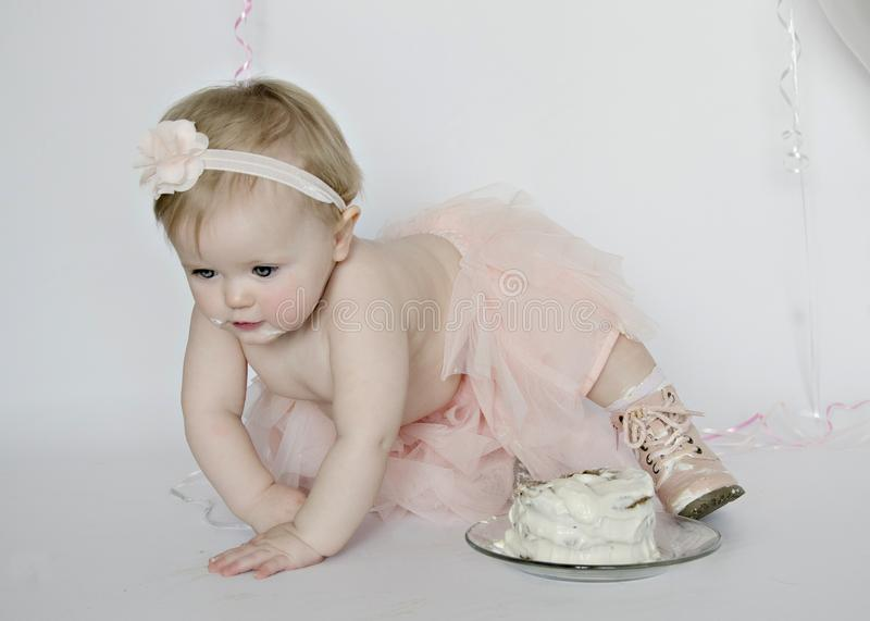 Birthday Cake Smash gets messy!. Crawling through first birthday cake session! Messy boots and pink tutus stock image