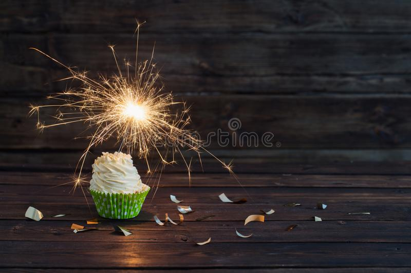 Birthday cake with sparkler on old wooden background stock photography