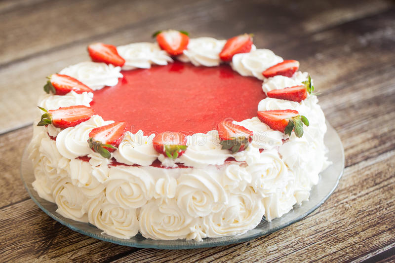 Birthday cake with strawberries and cream roses. Birthday cake with fresh strawberries and white cream roses on wood background stock image