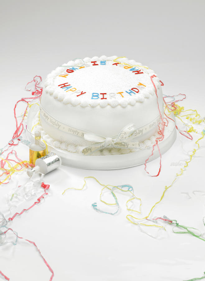 Birthday cake and streamers. A white birthday cake with streamers on a white surface royalty free stock photography