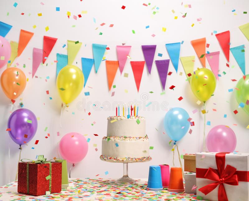 Birthday cake on a table. Against a wall with decoration flags and balloons stock photos