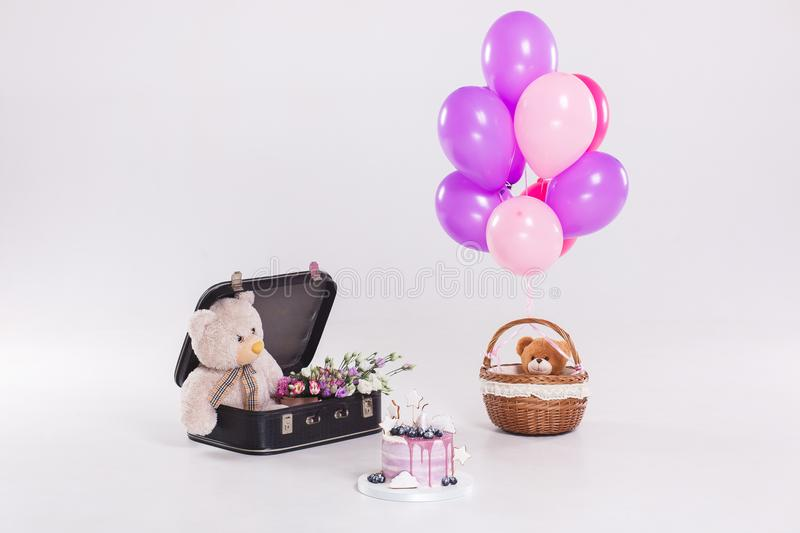 Birthday cake, teddy bear in vintage suitecase and balloons on white background royalty free stock photography