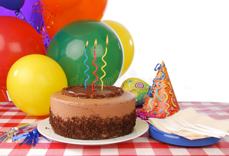 Birthday cake with three candles. A birthday cake and balloons with whitespace for copy royalty free stock images