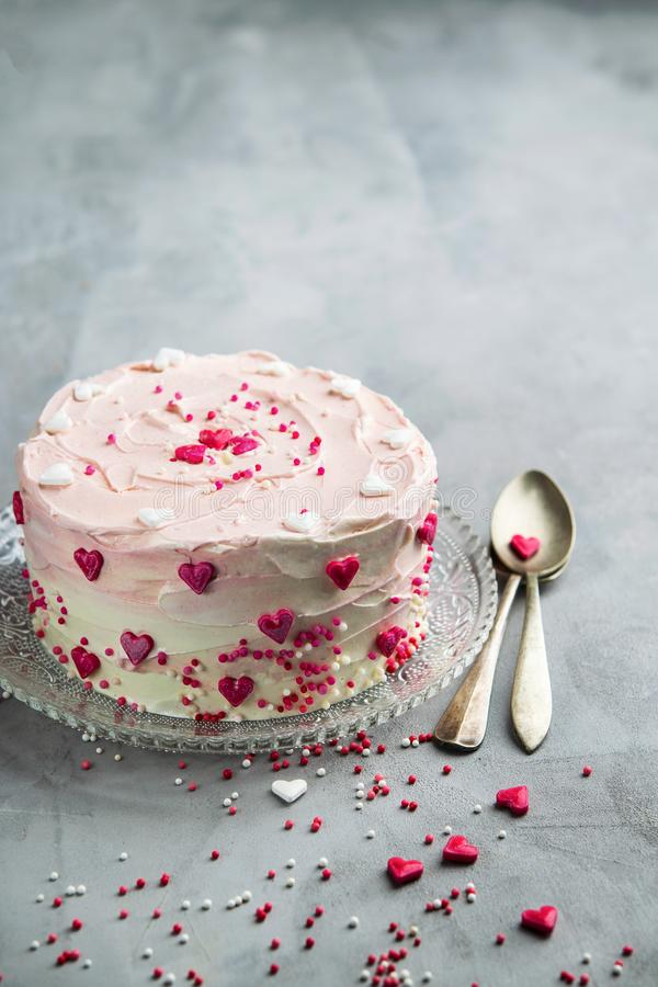 Birthday cake for Valentine`s Day with pink hearts and colorful sprinkles. Valentine`s day card background with copy space. Vertical stock images