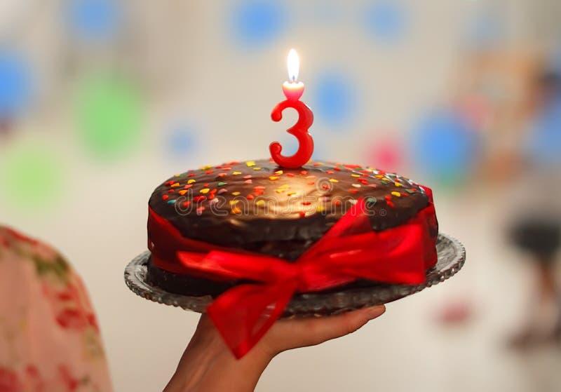 Birthday cake. Woman hand holding a chocolate birthday cake for children royalty free stock photo