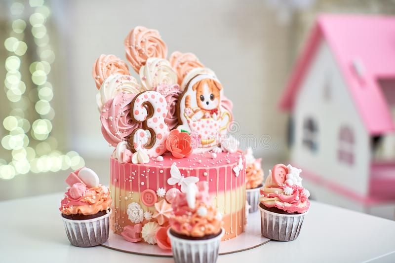 Birthday cake for 3 years decorated with butterflies gingerbread kitten with icing and the number three. meringue pale pink in the royalty free stock photos