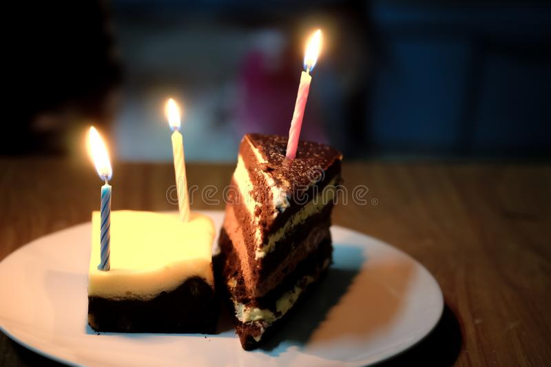 Birthday cakes distributed in a plate with candles. In the small family royalty free stock image