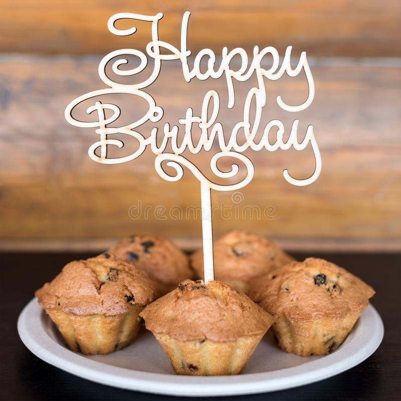 Birthday cakes and muffins with wooden greeting sign on rustic background. Wooden sing with letters Happy Birthday and. Holiday sweets stock images