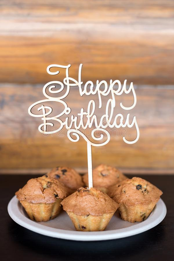 Birthday cakes and muffins with wooden greeting sign on rustic background. Wooden sing with letters Happy Birthday and. Holiday sweets stock photo