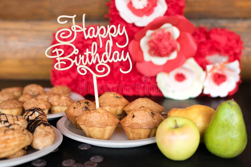 Birthday cakes and muffins with wooden greeting sign on rustic background. Wooden sing with letters Happy Birthday and. Holiday sweets stock image