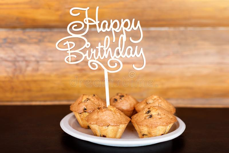 Birthday cakes and muffins with wooden greeting sign on rustic background. Wooden sing with letters Happy Birthday and. Holiday sweets royalty free stock images