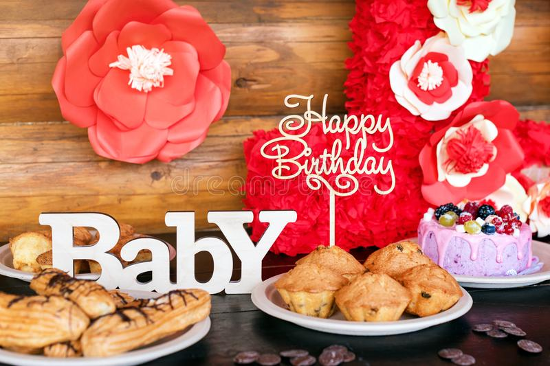 Birthday cakes and muffins with wooden greeting signs on rustic background. Wooden sing with letters Happy Birthday. Baby and holiday sweets royalty free stock image